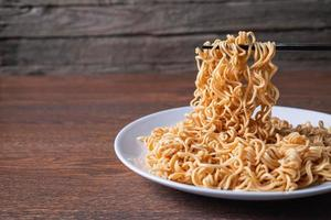 Pair of chopsticks picking up instant noodles on a white plate on a wooden table
