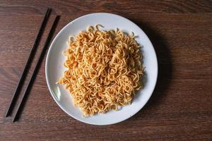 Instant noodles on a white plate next to pair of chopsticks on a wooden table