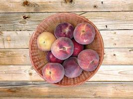 Peaches in a wicker basket on a wooden table background photo