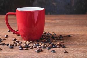 Café en una taza de café roja junto a los granos de café derramados sobre una mesa de madera