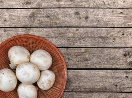 Setas blancas en una cesta de mimbre sobre un fondo de mesa de madera