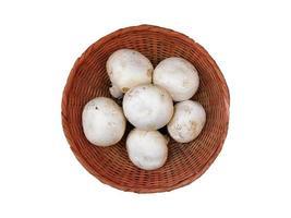 Setas blancas en una cesta de mimbre aislado sobre un fondo blanco.