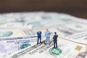 Gente de negocios en miniatura con fondo de billetes de dólar estadounidense foto