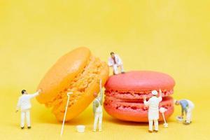 Pintores en miniatura para colorear macarrones sobre un fondo amarillo foto