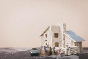 Miniature people sitting at home with coins, investment and growth in business concept
