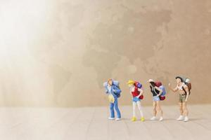 Miniature travelers with backpacks walking on a map, travel and adventure concept photo