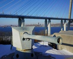 Landscape view the Voroshilov Battery and the Russky Bridge against a clear blue sky in Vladivostok, Russia photo