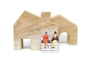 Marido y mujer en miniatura sentados delante de una casa sobre un fondo blanco, concepto de familia foto