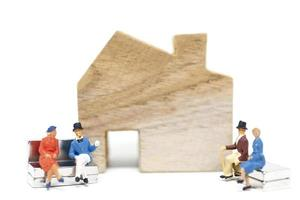 Miniature husband and wife sitting in front of a house on a white background, family concept