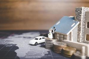 Miniature bride and groom with coins in front of a home, successful family concept