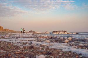 La gente caminando por la playa de cristal contra un colorido cielo nublado en Vladivostok, Rusia foto