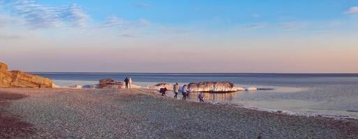 Panorama de la gente caminando por la playa de cristal contra un colorido cielo nublado en Vladivostok, Rusia foto