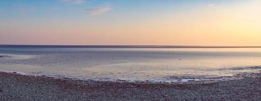 panorama marino de playa y colorido cielo nublado foto
