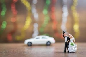 Miniature bride and groom on a wooden floor with colorful bokeh background, successful family concept