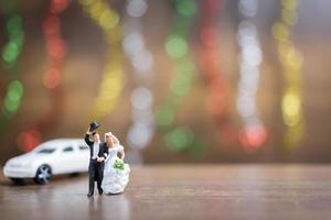 La novia y el novio en miniatura sobre un piso de madera con un colorido fondo bokeh, concepto de familia exitosa foto