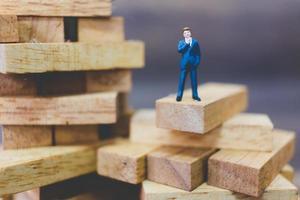 Empresario en miniatura de pie sobre un bloque de madera foto