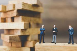 Empresarios en miniatura de pie sobre un bloque de madera foto