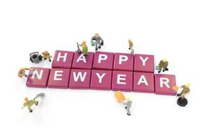 Miniature workers building the word Happy New Year on a white background photo