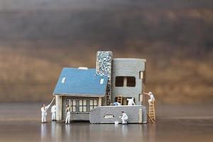 Trabajadores en miniatura pintando un nuevo hogar, concepto de renovación foto