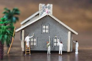 Miniature workers painting a new home, renovation concept