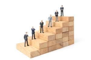 Empresarios en miniatura de pie sobre bloques de madera aislado sobre un fondo blanco. foto