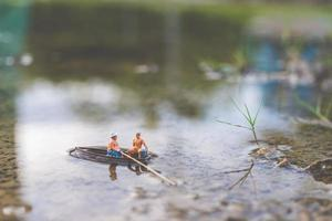 Miniature fishermen fishing on a boat photo