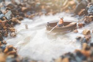 Miniature fisherman fishing on a boat photo