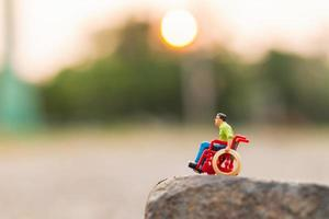 Miniature disabled man sitting in a wheelchair on a rock cliff photo