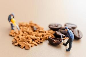 Equipos en miniatura trabajando juntos en la mezcla de café. foto