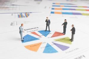 Miniature businessmen standing on a paper graph chart, developing teamwork concept photo