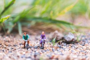 Miniature travelers riding bicycles, exploring the world concept