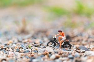 Miniature traveler riding a bicycle, exploring the world concept