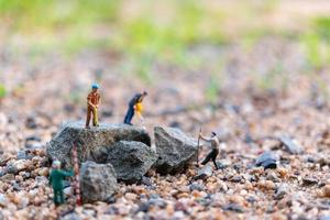 Miniature workers on a rock, teamwork concept