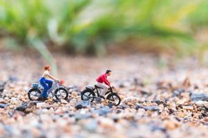 Viajeros en miniatura en bicicleta, explorando el concepto del mundo. foto