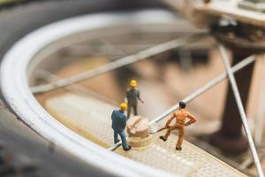 Miniature mechanics repairing a bicycle, workshop concept