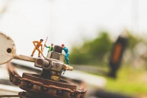 Mecánica en miniatura reparando una bicicleta, concepto de taller foto