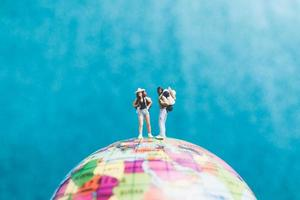 Miniature travelers with backpacks standing on a world globe and walking to a destination photo