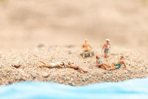 Miniature people wearing swimsuits relaxing on a beach, summer concept photo