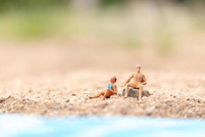 Gente en miniatura vistiendo trajes de baño relajándose en una playa, concepto de verano foto