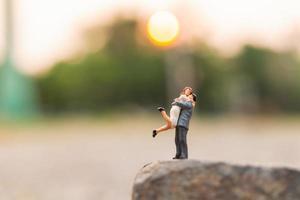 Pareja en miniatura de pie sobre un acantilado de roca foto
