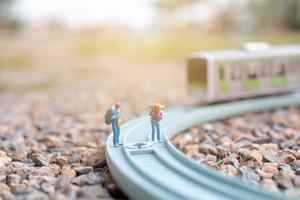 Miniature couple backpackers walking on a railway, travel concept photo