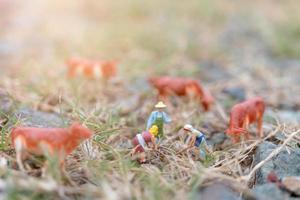Jardineros en miniatura que trabajan en el campo, el agricultor y el concepto de jardinería
