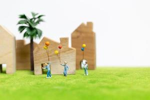 Miniature family walking in a field with balloons, happy family time concept