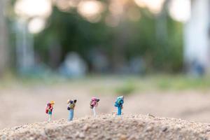 Viajeros en miniatura con mochilas caminando sobre arena, concepto de viaje y aventura