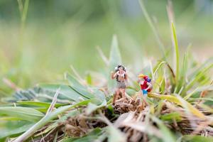 Miniature traveler with backpacks walking in the field, travel and adventure concept photo