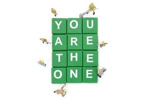 Miniature workers building the words You Are The One on a white background photo