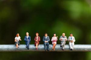 Empresarios en miniatura sentados en un cable con un fondo verde, concepto de equipo empresarial foto
