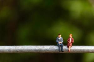 Miniature businesspeople sitting on a wire with a green background, business team concept