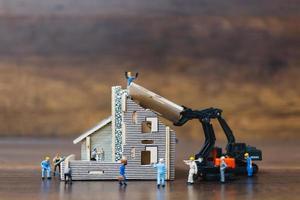 Trabajadores en miniatura construyendo un hogar, concepto de renovación del hogar foto