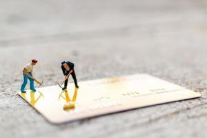 Miniature workers working on a credit card, business and finance concept photo